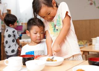 年上の子どもが年下の子どもを手伝う様子